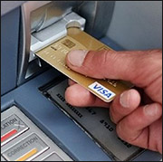 person using debit card at an ATM